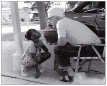 A child stops to chat with Bill Biederman in the carport of his apartment at Hope Meadows. (Photo credit: Alex Harris)